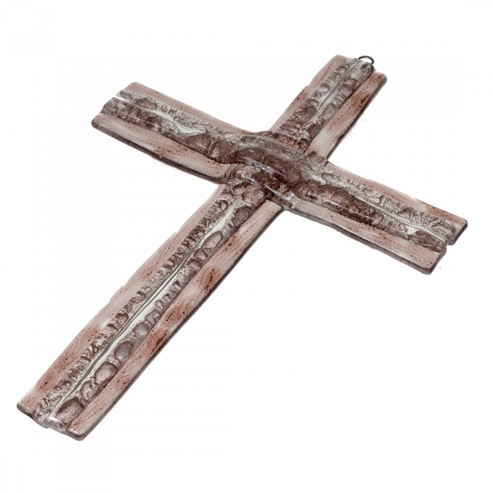 A glass cross on a wall of brown layered